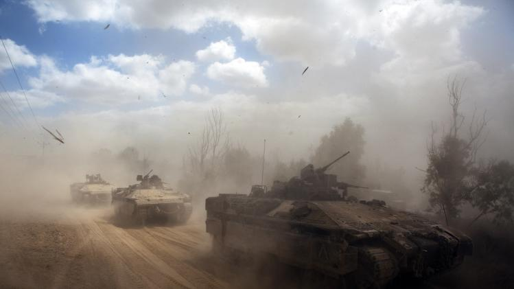 Israeli APCs drive near the Israeli border with Gaza as the come out of the Gaza Strip