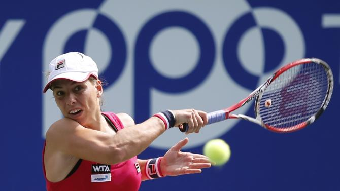 Marina Erakovic of New Zealand returns a shot to Casey Dellacqua of Australia during their Pan Pacific Open women's singles tennis match in Tokyo
