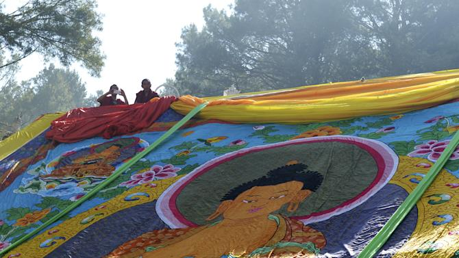 Tibetan monks look on above a giant Thangka, a religious silk embroidery or painting displaying a Buddha portrait, at a prayer ceremony to mark the Buddha's birthday, in Kangding county
