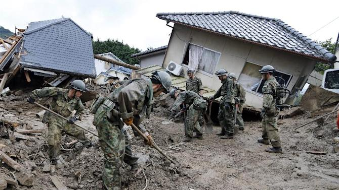 Japan Ground Self Defense Force personnel search for missing residents in a mud-ridden residential area following a massive landslide in Hiroshima, western Japan, Thursday, Aug. 21, 2014. Rain-sodden slopes collapsed in torrents of mud, rock and debris Wednesday on the outskirts of Hiroshima city, killing more than 30 people and leaving a several missing, Japanese police said. (AP Photo/Kyodo News) JAPAN OUT