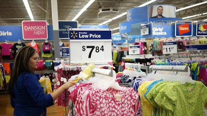 An employee cleans a clothes rack at the Walmart Supercenter in Bentonville