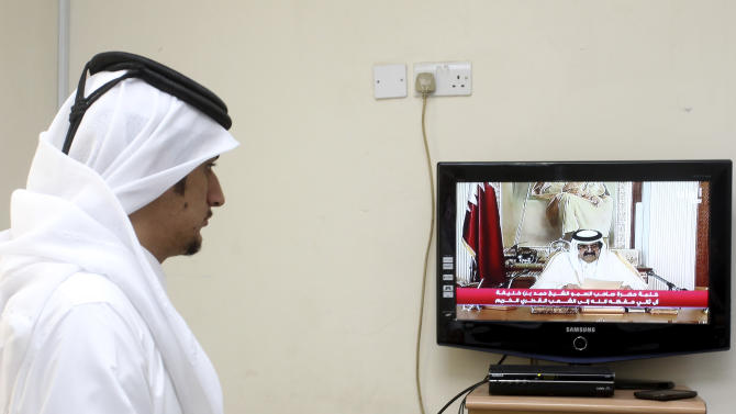 A man watches a televised address by Qatar's Emir Sheik Hamad bin Khalifa Al Thani, in Doha, Qatar,Tuesday, June 25, 2013. Qatar's ruler said Tuesday he has transferred power to the 33-year-old crown prince in an anticipated move that puts a new generation in charge of the Gulf nation's vast energy wealth and rising political influence. (AP Photo/Osama Faisal)