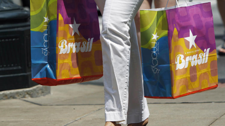 In this July 3, 2012 photo, a pedestrian carries bags after shopping at Macy's in downtown Chicago. Shoppers, worried about jobs and the overall economy, pulled back on spending in June, resulting in tepid sales for many retailers. (AP Photo/Sitthixay Ditthavong)