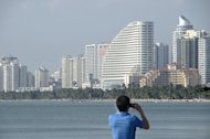 A man takes photos of buildings in the seaside city of Sanya, in China&#39;s southern Hainan province, on January 19, 2013. Chinese who cannot afford to buy a home have been frustrated by high housing costs for years