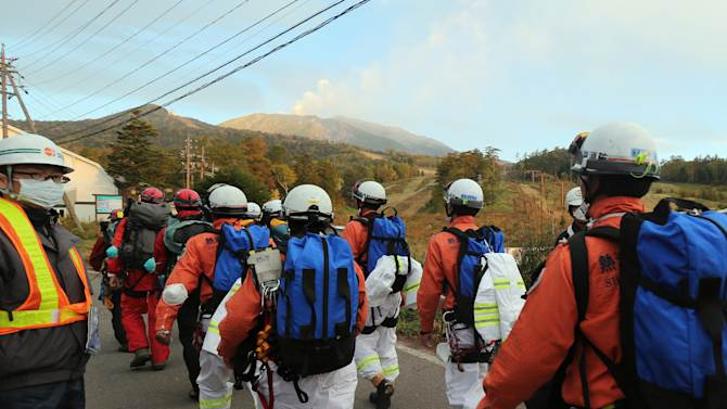 Rescue workers and police climb Mount Ontake from Otaki village in Nagano prefecture, on October 4, 2014, one week after the volcano erupted