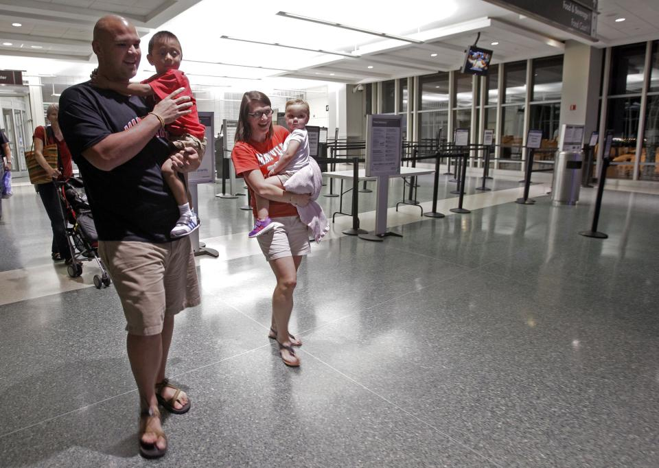 CORRECTS SPELLING OF DAUGHTER'S FIRST NAME TO ELLYSON INSTEAD OF ELLISON - In this Saturday, Sept. 8, 2012 photo, Ryan and Jessica Hooker arrive at McGhee Tyson Airport in Louisville, Tenn., from Guatemala City, with their newly adopted son Daniel and their daughter Ellyson. (AP Photo/Wade Payne)