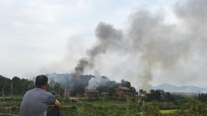 A man looks at smoke from a fireworks plant after an explosion in Liling, Hunan province