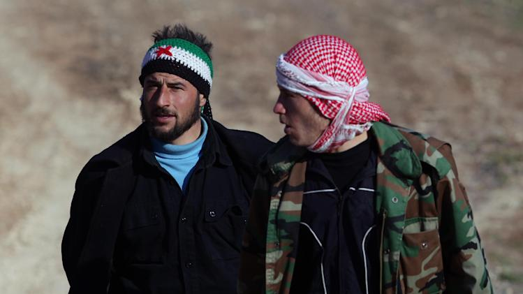 Two Syrians fleeing violence in their country, walk toward a refugee camp after they cleared barbed wire to enter Turkey near Reyhanli, Turkey, Saturday, March 17, 2012. News reports say about 1,000 Syrian refugees arrived on Wednesday escaping violence. (AP Photo/Burhan Ozbilici)
