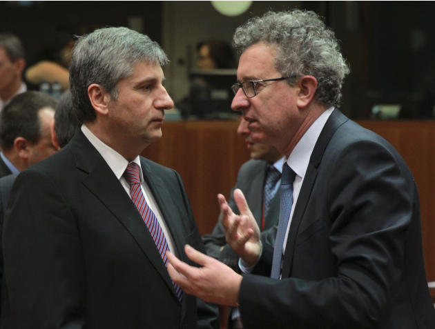 Austrian Finance Minister Michael Spindelegger, left, talks with his Luxembourg's counterpart Pierre Gramegna at the start of an EU finance ministers meeting at the European Council building in Br