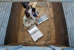 Polling officials check electronic voting machines in a truck after collection them at a distribution centre in Allahabad