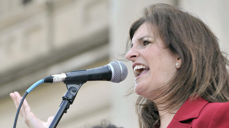 "Rep Lisa Brown, D-West Bloomfield reads her part during a performance of ""The Vagina Monologues""  with 10 other lawmakers and several actresses on the Michigan Statehouse steps, Monday, June 18, 2012, in Lansing, Mich. Brown, who says she was barred from speaking in the Michigan House because Republicans objected to her saying ""vagina"" during debate over anti-abortion legislation, performed ""The Vagina Monologues"" with a hand from the author Eve Ensler. (AP Photo/Detroit News, Dale G. Young)"