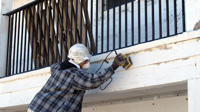 A construction worker sands the outside of the Sundowner Motel, Thursday, April 18, 2013, in Albuquerque, N.M. The historic Route 66 motor lodge where Bill Gates and Paul Allen launched Microsoft is being redeveloped into apartments as part of a neighborhood revival project. (AP Photo/Russell Contreras)