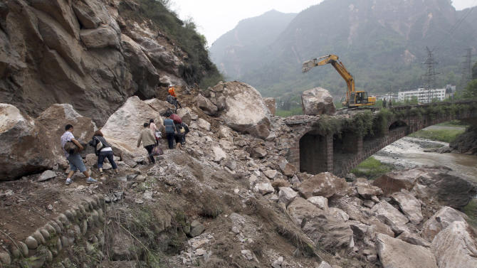In this photo released by China's Xinhua News Agency, people walk on rocks fallen due to a landslide triggered by a strong quake in Baosheng Township, Lushan County, southwest China's Sichuan Province, Sunday, April 21, 2013. The 7.0-magnitude earthquake hit Lushan County Saturday morning, killing more than 200 people, Xinhua said. (AP Photo/Xinhua, Zhang Xiaoli) NO SALES
