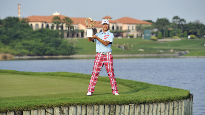 Guan Tianlang of China poses with the winner's trophy after the Asia-Pacific Amateur Championship golf at Amata Spring Country Club in Chonburi, Thailand Sunday, Nov. 4, 2012. (AP Photo/AAC, Paul Lakatos) NO LICENSING