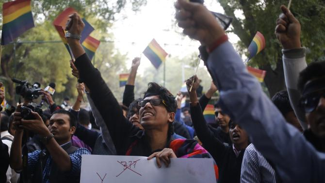 Gay rights activists wave flags and shout slogans as they attend protest against a verdict by the Supreme Court in New Delhi