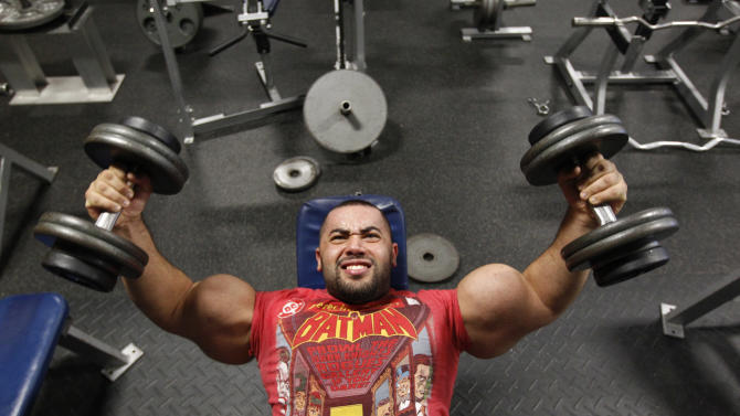 In this photo taken, Friday, Nov. 16, 2012, Egyptian Body builder Moustafa Ismail lifts weights during his daily workout at World Gym in Milford, Mass. Ismail has been given the title of world's biggest arms, biceps and triceps, by the Guinness Book of World Records. (AP Photo/Stephan Savoia)