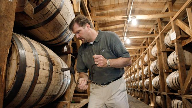 File – In this May 20, 2009, file photo, Jeff Arnett, the master distiller at the Jack Daniel Distillery in Lynchburg, Tenn., drills a hole in a barrel of whiskey in one of the aging houses at the distillery. Jack Daniel's is fighting efforts in the state Legislature to dial back the legal definition of Tennessee whiskey, including a provision that requires the spirit to be aged in new oak barrels. (AP Photo/Mark Humphrey, file)