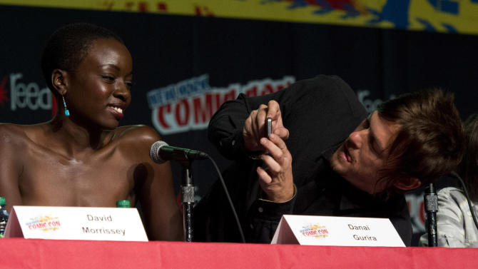 """IMAGE DISTRIBUTED FOR AMC - Danal Gurira, left, and Norman Reedus of the the AMC show """"The Walking Dead"""" are seen during a panel at NYC-Comic-Con on Saturday, Oct. 13, 2012  in New York. (Photo by Charles Sykes/Invision for AMC/AP Images)"""