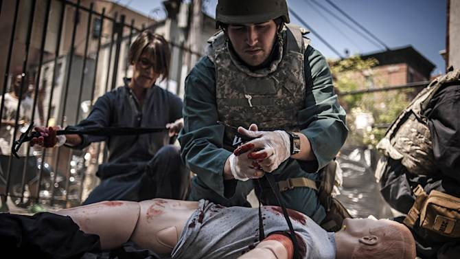 In this June 20, 2013 photo provided by Reporters Instructed in Saving Colleagues (RISC), Tanya Bindra, left, and Joey Daoud, right, administer care to a training dummy simulating an injured person during a battlefield medical response training workshop for freelance journalists, in the South Bronx area of New York as onlookers watch from a sidewalk. (AP Photo/RISC, James Lawler Duggan)