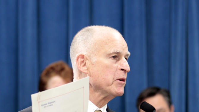 Gov. Jerry Brown displays the proclamation he signed declaring the  end to the prison overcrowding emergency, during a news conference at the Capitol in Sacramento, Calif., Tuesday, Jan. 8, 2013.   Brown is challenging a federal court order for California to reduce its inmate population and is calling for federal judges to return control of prisons to the state.  Brown's proclamation  will allow the state to phase out the use of private out-of-state prison beds for California inmates starting in July of 2013.(Photo/Rich Pedroncelli)