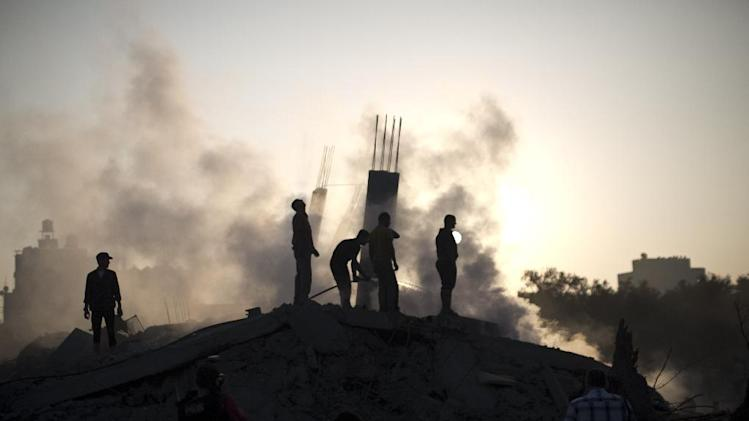Palestinian men inspect the site of an Israeli military strike in Gaza City on July 8, 2014