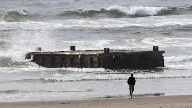 In this file photo from  Wednesday, June 6, 2012, a man looks at a 70-foot-long dock with Japanese lettering that washed ashore on Agate Beach Wednesday, June 6, 2012, in Newport, Ore.  More than a year after a tsunami devastated Japan, killing thousands of people and washing millions of tons of debris into the Pacific Ocean, neither the U.S. government nor some West Coast states have a clear plan for how to clean up the rubble that floats to American shores. There is also no firm handle yet on just what to expect. The Japanese government estimates that an enormous 1.5 million tons of debris is floating in the ocean from the catastrophe. Some experts in the United States think the bulk of that trash will never reach shore, while others fear a massive, slowly-unfolding environmental disaster. (AP Photo/Rick Bowmer, File)