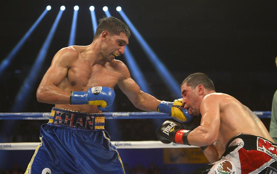 Amir Khan, left, of Great Britain connects with Carlos Molina during their WBC silver super lightweight title bout, Saturday, Dec. 15, 2012, in Los Angeles.  (AP Photo/Mark J. Terrill)