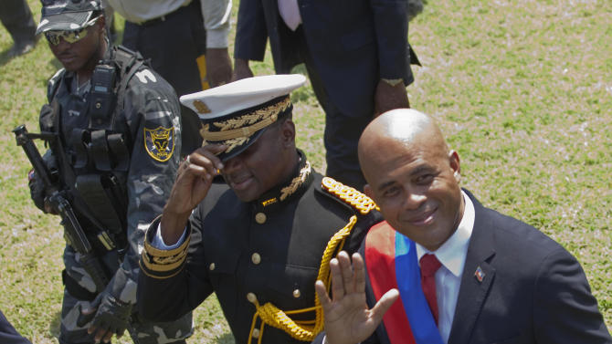 """Haiti's newly-sworn-in President Michel Martelly, right, walks with Haiti's Chief of Police Mario Andresol during Haiti's presidential inaugural ceremony at the National Palace in Port-au-Prince, Haiti, Saturday May 14,  2011. The 50-year-old performer known to Haitians as """"Sweet Micky"""" was swept to power in a March 20 presidential runoff by Haitians tired of past leaders who failed to provide even basic services, such as decent roads, water and electricity in the Western Hemisphere's poorest country. (AP Photo/Ramon Espinosa)"""