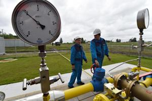 Employees look at a pipeline at the new East Poltava …