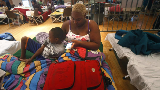 Brandy Battle, of Davant, La., sits on a cot with her son Patrick Bell, 5, on her 27th birthday and the anniversary of Hurricane Katrina, at an evacuation shelter after Isaac made landfall as a hurricane, in Belle Chasse, La., Wednesday, Aug. 29, 2012. (AP Photo/Gerald Herbert)