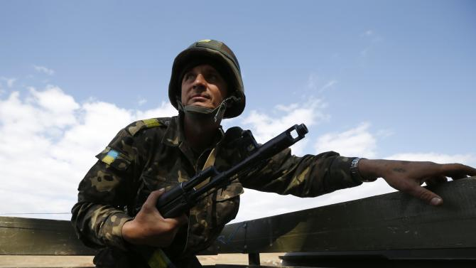 A Ukrainian serviceman observes his surroundings as he rides on a military truck near the eastern Ukrainian town of Pervomaysk