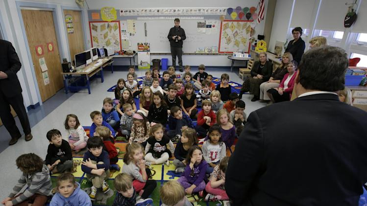 New Jersey Gov. Chris Christie, back to camera, visits a group of kindergarten, first and second grade students at the recently reopened Stone Harbor Elementary school in Stone Harbor, N.J., Wednesday, March 20, 2013. The school, one of eight in the state heavily damaged by Superstorm Sandy, is the first to reopen. The students attended schools in Avalon while their school was repaired. (AP Photo/Mel Evans)