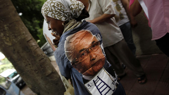 """An Egyptian woman wears a poster of presidential candidate Ahmed Shafiq on her shirt during a press conference at Shafiq's office in Cairo, Egypt, Saturday, May 26, 2012. Egyptian presidential candidate Ahmed Shafiq paid tribute Saturday to the """"glorious revolution"""" that toppled Hosni Mubarak, a dramatic turn-around for the former regime official who fought his way into the runoff elections by appealing to public disenchantment with last year's uprising. (AP Photo/Khalil Hamra)"""
