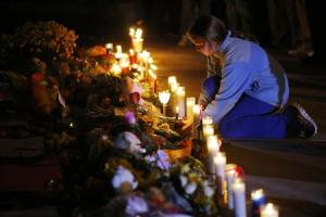 A girl lights a candle at a makeshift memorial for teacher Colleen Ritzer outside the high school where she taught in Danvers