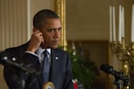 US President Barack Obama adjusts his earpiece during a press conference with Japanese Prime Minister Yoshihiko Noda in the East Room of the White House in Washington