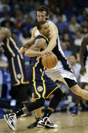 Orlando Magic's Hedo Turkoglu, right, reaches in to try to steal the ball from Indiana Pacers' George Hill during the first half of Game 4 of an NBA first-round playoff basketball series, Saturday, May 5, 2012, in Orlando, Fla. (AP Photo/John Raoux)