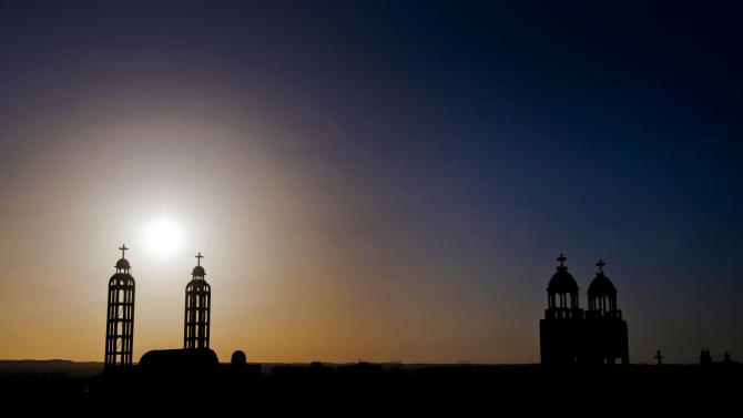 In this Tuesday, Dec. 18, 2012 photo, towers of churches are silhouetted against the sun in the village of El-Aziyah near the city of Assiut, southern Egypt. After a campaign of intimidation by Islamists, most Christians in this southern Egyptian province were too afraid to participate in last week's referendum on an Islamist-drafted constitution they desperately oppose, residents say. Some of the few who dared try to reach polls were pelted by stones. The disenfranchising hikes Christians' worries over their future under Egypt's empowered Islamists, but some young members of the community are starting to push back.(AP Photo/Petr David Josek)