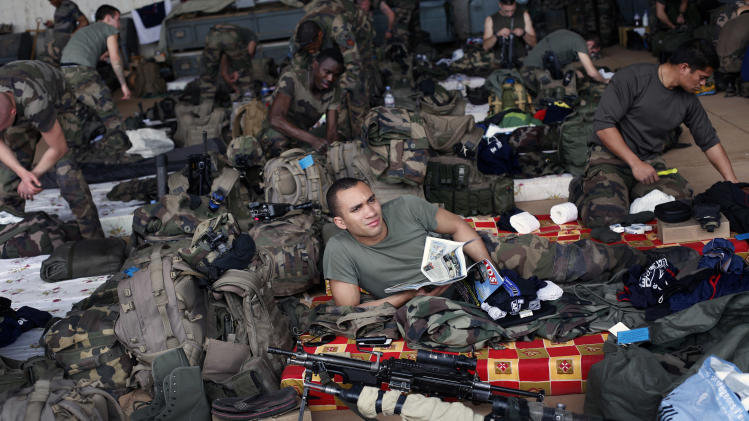 French troops gather in a hangar at Bamako's airport Tuesday Jan. 15, 2013.  French forces led an all-night aerial bombing campaign Tuesday to wrest control of a small Malian town from armed Islamist extremists who seized the area, including its strategic military camp. A a convoy of 40 to 50 trucks carrying French troops crossed into Mali from Ivory Coast as France prepares for a possible land assault. Several thousand soldiers from the nations neighboring Mali are also expected to begin arriving in coming days. (AP Photo/Jerome Delay)