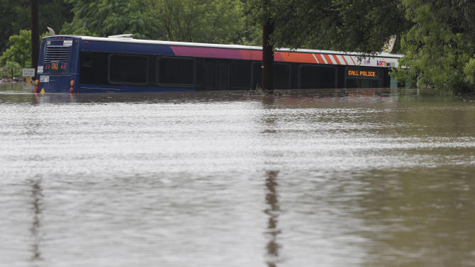 A San Antonio metro bus sits in floodwaters after it was swept off the road during heavy rains, Saturday, May 25, 2013, in San Antonio. (AP Photo/Eric Gay)