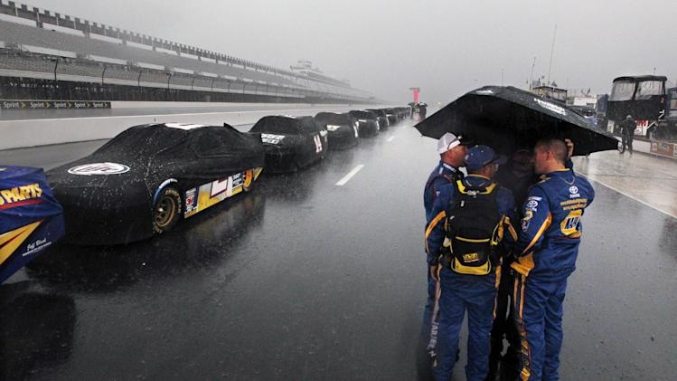Crew members stand in the pits in a downpour that shortened the NASCAR Sprint Cup Series auto race, Sunday, Aug. 5, 2012, at Pocono Raceway in Long Pond, Pa. Jeff Gordon won. (AP Photo/Mel Evans)