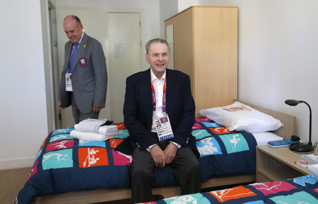 In this Monday, July 23, 2012 photo, IOC President Jacques Rogge, center, sits on a bed as he is accompanied by Charles Allen, village mayor, during his visit to the Athletes' Village at the Olympic Park, in London. More than 1 million items from the athletes village and Olympics Park are on sale here, and they'll be ready for collection right after the Paralympic Games end in early September. Included are: night stands, lamps, umpire's chairs and even beanbags. (AP Photo/Jae C. Hong)