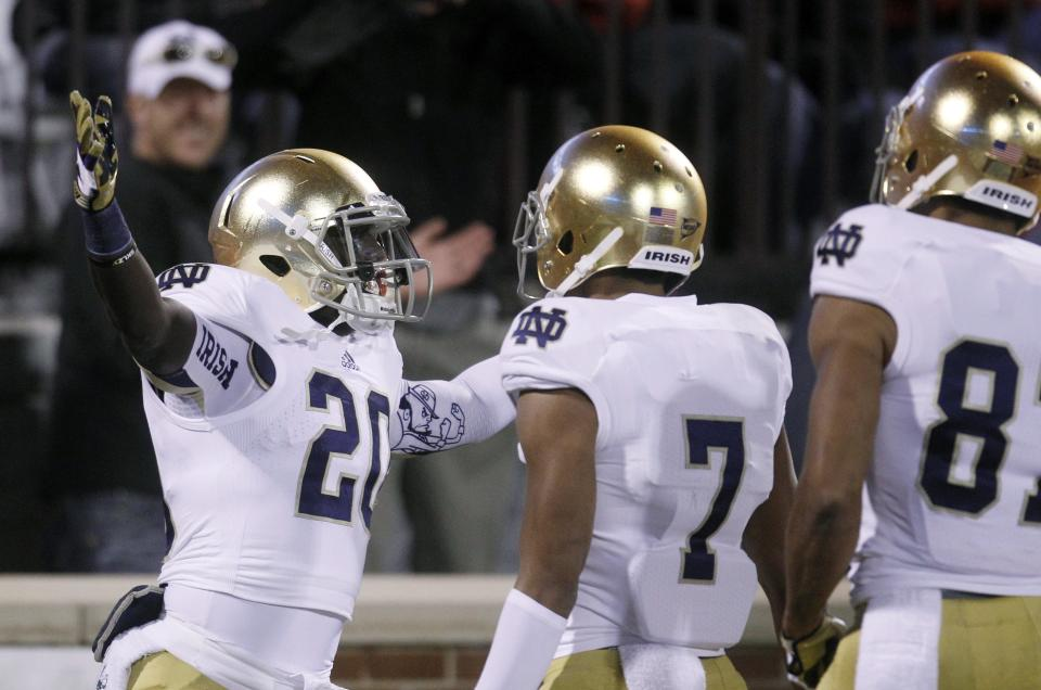 Notre Dame running back Cierre Wood celebrates his touchdown against Oklahoma with teammates T.J. Jones (7)and Daniel Smith, right, in the first quarter of an NCAA college football game in Norman, Okla., Saturday, Oct. 27, 2012. (AP Photo/Sue Ogrocki)