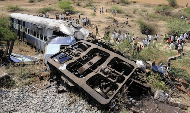 Onlookers gather near the damaged coach of a passenger train at the site of a train collision in Penneconda town in Anantapur