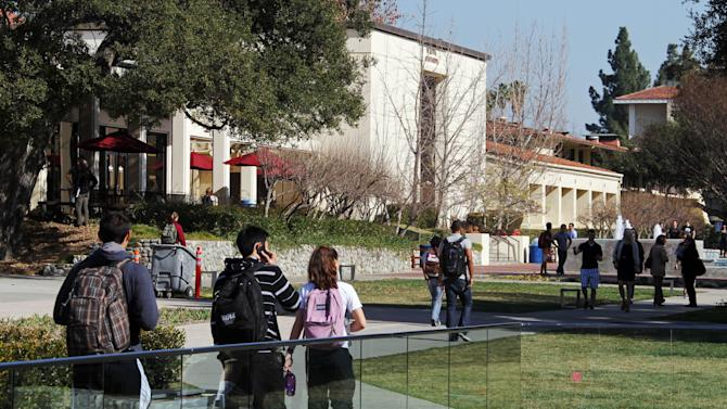 """In this Thursday, Feb. 2, 2012 photo, students walk through the campus of Claremont McKenna College in Claremont, Calif. When US News & World Report debuted its list of """"America's Best Colleges"""" nearly 30 years ago, the magazine hoped its college rankings would be a game-changer for students and families. Arguably, they've had a much bigger effect on colleges themselves. A senior administrator at Claremont McKenna, a highly regarded California liberal arts college, resigned after acknowledging he falsified college entrance exam scores for years to rankings publications such as US News. The scale was small: submitting scores just 10 or 20 points higher on the 1600-point SAT math and reading exams. (AP Photo/Reed Saxon)"""