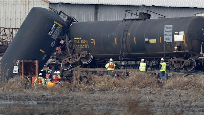 Officials examine the area around a derailed freight train tank car in Paulsboro, N.J., Friday morning, Nov. 30, 2012. People in three southern New Jersey towns were told Friday to stay inside after a freight train derailed and several tanker cars carrying hazardous materials toppled from a bridge and into a creek. At least one tanker car may contain vinyl chloride, Gloucester County Emergency Management director J. Thomas Butts told WPVI-TV. (AP Photo/Mel Evans))