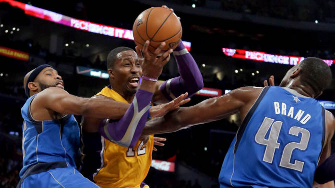 Los Angeles Lakers' Dwight Howard, center, is defended by Dallas Mavericks' Vince Carter, left, and Elton Brand in the first half of an NBA basketball game in Los Angeles, Tuesday, Oct. 30, 2012. (AP Photo/Jae C. Hong)