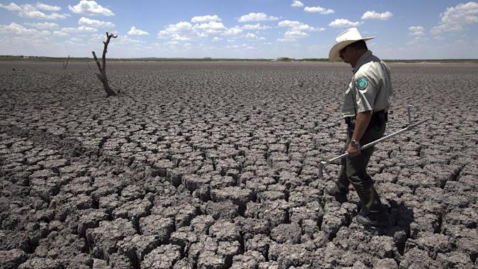 FILE - In this Aug 3, 2011 file photo, Texas State Park police officer Thomas Bigham walks across the cracked lake bed of O.C. Fisher Lake, in San Angelo, Texas. A combination of the long periods of 100 plus degree days and the lack of rain in the drought -stricken region has dried up the lake that once spanned over 5400 acres. From Dallas to far-flung ranches and rice farms, Texans and officials are trying to capitalize on heightened drought awareness by adopting conservation plans that will ease the next crisis. (AP Photo/Tony Gutierrez, File)