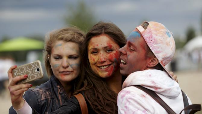 """People pose for a """"selfie"""" during the Holi festival, or the Festival of Colors, in Riga"""