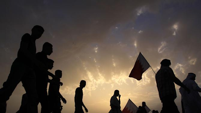 Bahraini anti-government protesters disperse carrying their flags Saturday, March 12, 2011, after a peaceful demonstration by tens of thousands outside the walls of King Hamad bin Isa Al Khalifa's Safriya palace in Sadad, Bahrain, southwest of the capital of Manama. (AP Photo/Hasan Jamali)