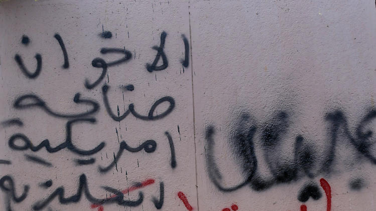 "An Egyptian man walks past Arabic writing on a wall that reads, ""the Muslim Brotherhood are an American and English invention,"" in Tahrir Square, Cairo, Egypt, Sunday, Dec. 9, 2012. Egypt's liberal opposition has called for more protests on Sunday after the president made concessions overnight that fell short of their demands to rescind a draft constitution going to a referendum on Dec. 15. (AP Photo/Hassan Ammar)"